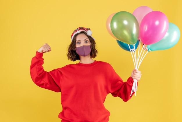 Jovem, vista frontal, segurando balões em máscara estéril em amarelo