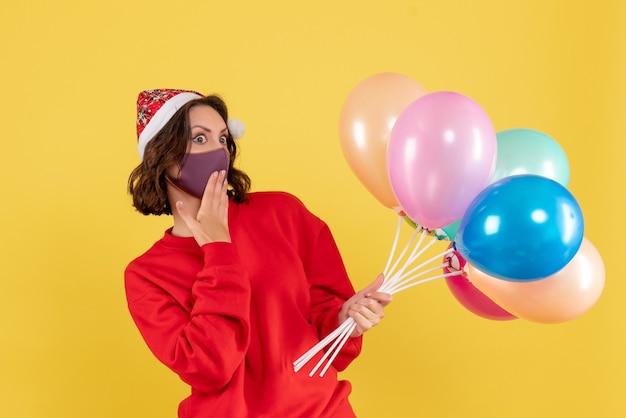 Jovem, vista frontal, segurando balões na máscara amarela