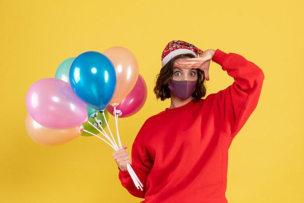 Jovem, vista frontal, segurando balões na máscara sobre a mulher de emoção de celebração de cor de ano novo de festa amarela
