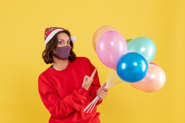 Jovem, vista frontal, segurando balões na máscara sobre o vírus amarelo cobiçoso festa emoção ano novo cor mulher