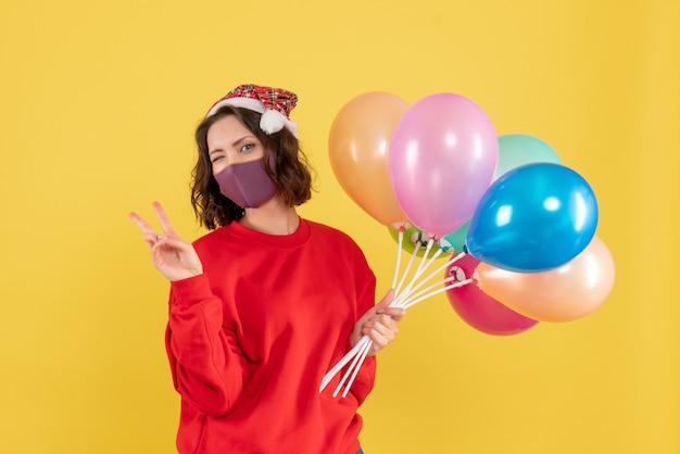 Jovem, vista frontal, segurando balões na máscara sobre o vírus da mesa amarela cobiçoso festa emoção ano novo cor mulher