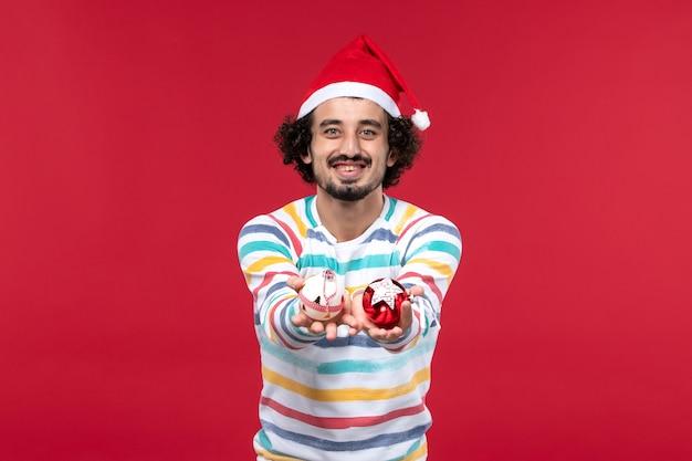 Jovem, vista frontal, segurando brinquedos de plástico na parede vermelha.