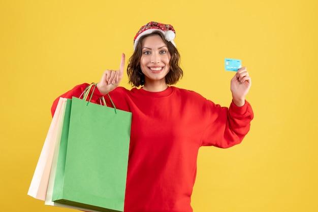 Jovem, vista frontal, segurando o cartão do banco e pacotes em amarelo