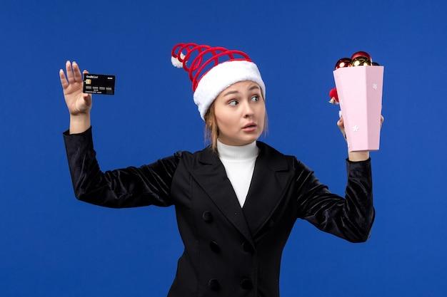 Jovem, vista frontal, segurando o cartão do banco na parede azul, brinquedos natalinos, emoções de ano novo