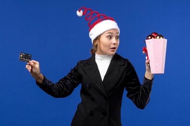Jovem, vista frontal, segurando o cartão do banco na parede azul dinheiro com emoção de ano novo
