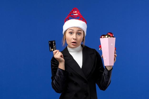 Jovem, vista frontal, segurando o cartão do banco na parede azul, feriado emocionante de ano