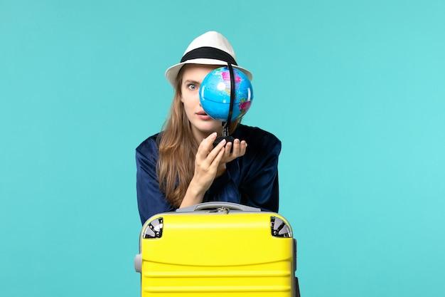Jovem, vista frontal, segurando o globo e se preparando para as férias no fundo azul feminino viagem viagem hidroavião férias