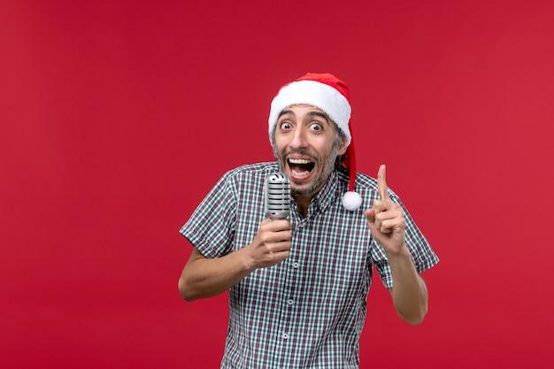 Jovem, vista frontal, segurando o microfone na parede vermelha, emoção, música, cantor, feriados