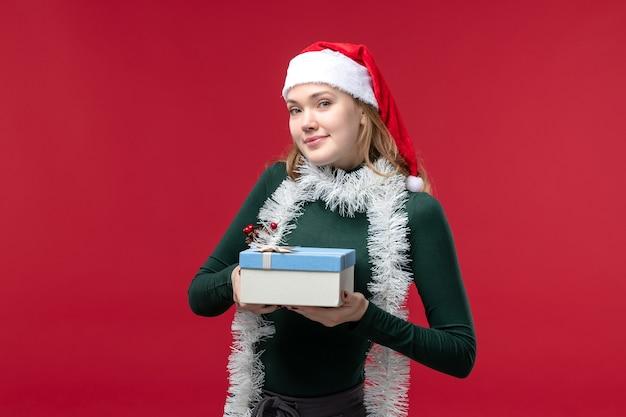 Jovem, vista frontal, segurando o presente de ano novo em fundo vermelho