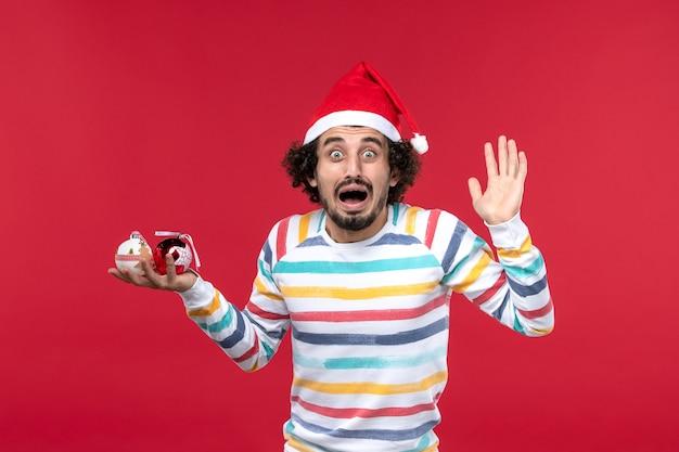 Jovem, vista frontal, segurando os brinquedos da árvore de natal na parede vermelha, ano novo, vermelho, humanos, feriados
