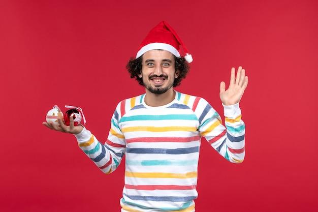 Jovem, vista frontal, segurando os brinquedos da árvore de natal na parede vermelha, feriado humano de ano novo, vermelho