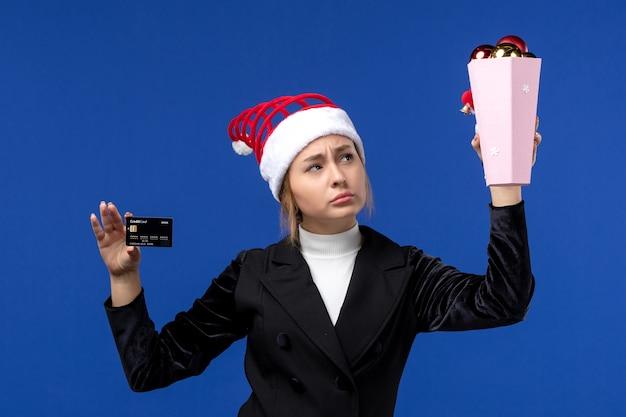 Jovem, vista frontal, segurando um cartão do banco em um brinquedo de parede azul, férias emocionantes de ano novo