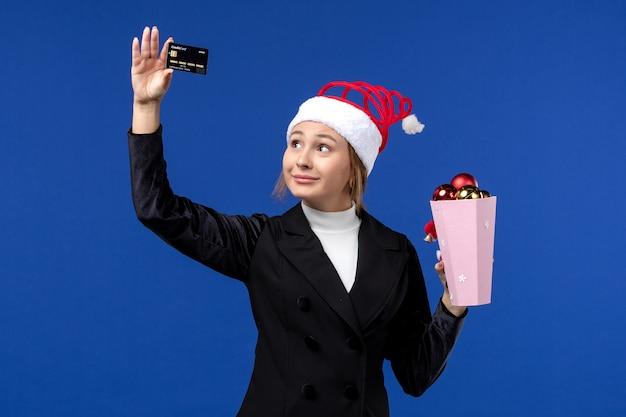 Jovem, vista frontal, segurando um cartão do banco no feriado de emoção de ano novo de brinquedo de parede azul