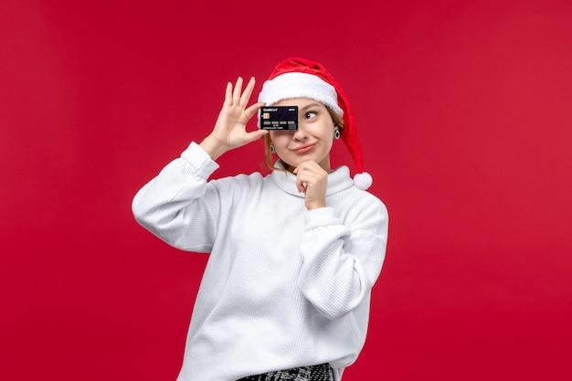 Jovem, vista frontal, segurando um cartão do banco sobre fundo vermelho