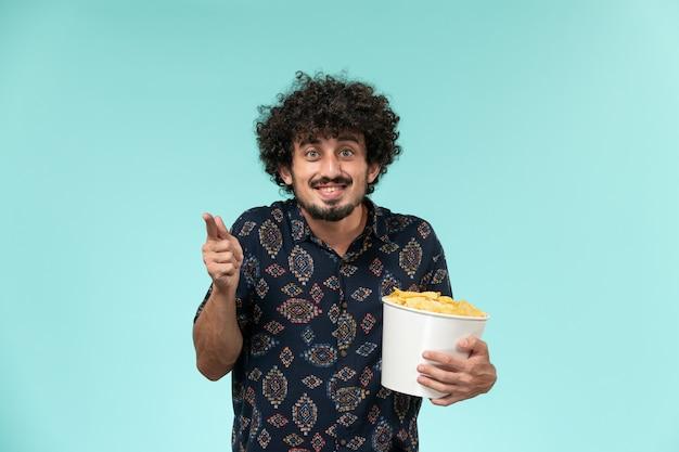 Jovem, vista frontal, segurando uma cesta com batatas cips e assistindo filme na parede azul.