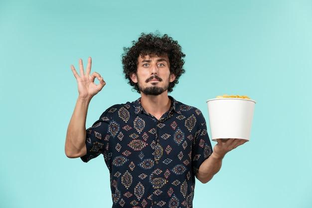 Jovem, vista frontal, segurando uma cesta com batatas cips na parede azul remoto filme cinema cinema teatro
