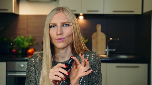 Jovem vlogger cheirando a perfume.