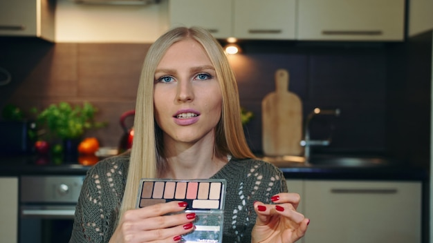 Jovem vlogger falando sobre sombra para os olhos de maquiagem.