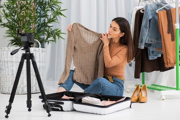 Jovem vlogger gravando com roupas