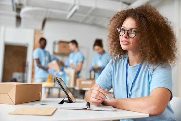 Jovem voluntária em uniforme azul olhando para o lado fazendo anotações enquanto trabalha no projeto de doação