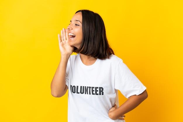 Jovem voluntária isolada em um fundo amarelo gritando com a boca bem aberta para o lado
