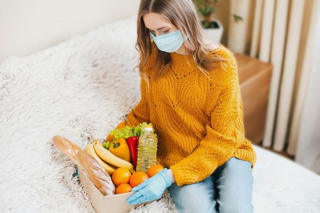 Jovem voluntário em uma máscara médica detém uma caixa de papelão com comida vegetariana, frutas e legumes e senta-se em um sofá, entrega em domicílio, coronovírus, quarentena, conceito de ficar em casa