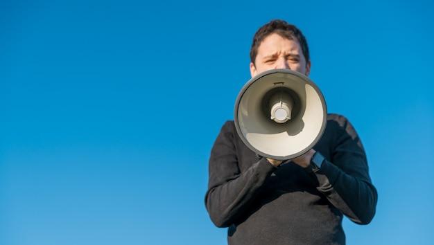 Jovem vozes em instruções de um megafone para o exercício. copie o espaço