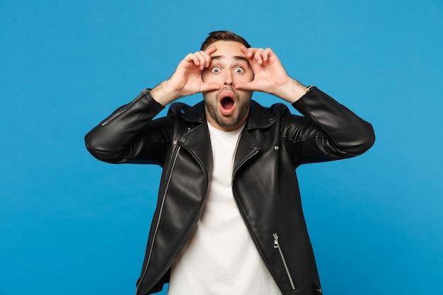 Jovem wow frustrado preocupado homem com a barba por fazer em camiseta branca de jaqueta preta, olhando a câmera isolada no retrato de estúdio de fundo de parede azul. conceito de estilo de vida de emoções sinceras de pessoas. simule o espaço da cópia.