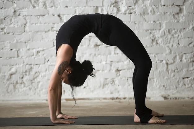 Jovem yogi atraente em urdhva dhanurasana pose, loft bac