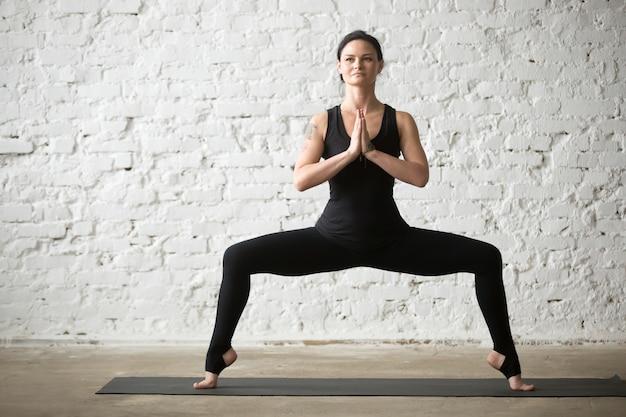 Jovem yogi atraente mulher em deusa pose, branco loft backgrou