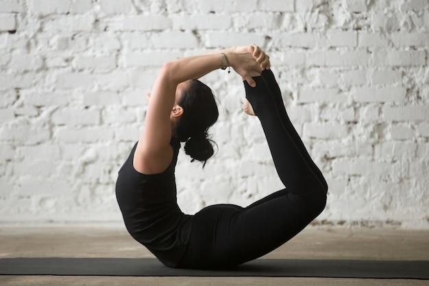 Jovem yogi mulher atraente em bow pose, branco loft background