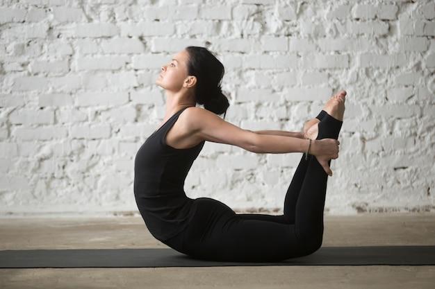 Jovem yogi mulher atraente em dhanurasana pose, loft branco de volta