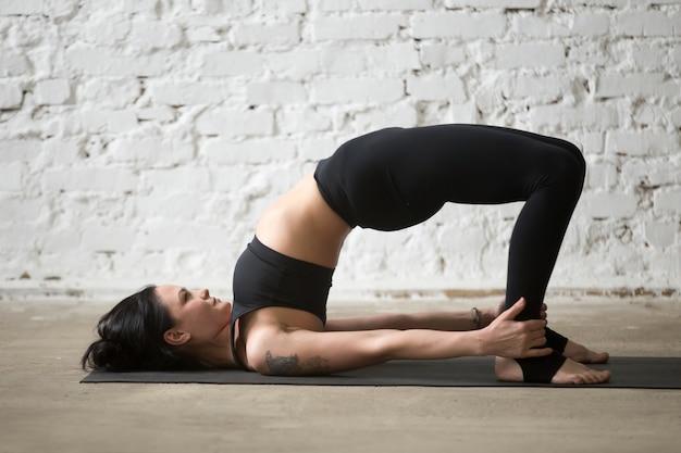 Jovem yogi mulher atraente em glute bridge pose, loft backgroun