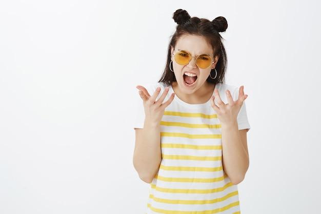 Jovem zangada posando com óculos de sol contra uma parede branca