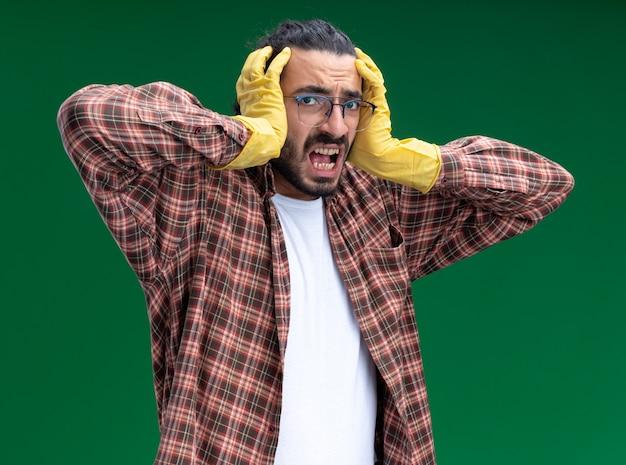 Jovem, zangado, bonito, faxineiro, usando camiseta e luvas, agarrou a cabeça isolada na parede verde