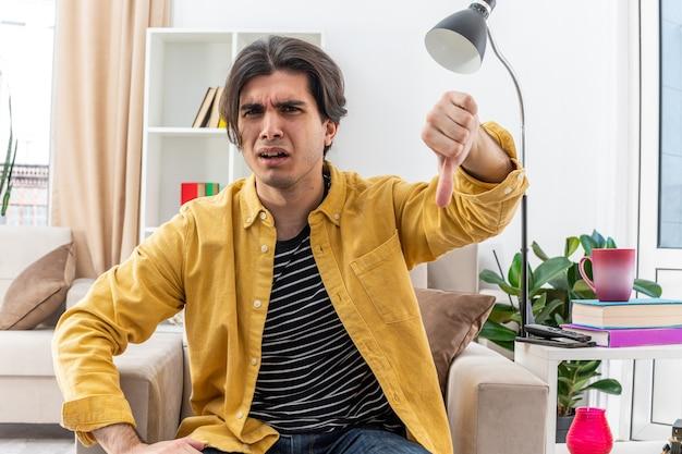 Jovem zangado com roupas casuais, mostrando os polegares para baixo, sentado na cadeira na sala de estar iluminada