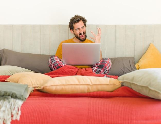 Jovem zangado com um laptop na cama