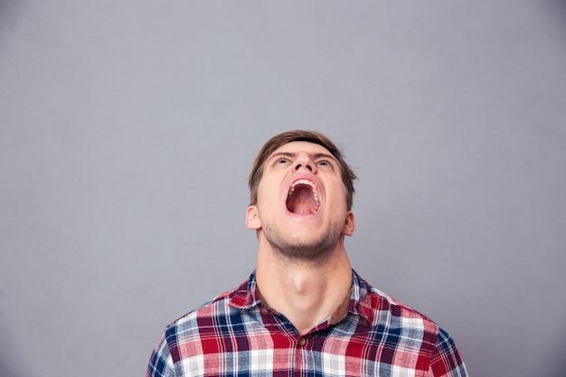 Jovem zangado e desesperado com uma camisa xadrez olhando para cima e gritando por cima da parede cinza