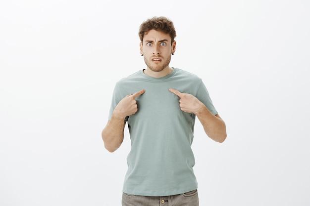 Jovem zangado e frustrado com cerdas na camiseta e nos brincos, apontando para si mesmo e franzindo a testa, sendo insultado ou ofendido pelo amigo