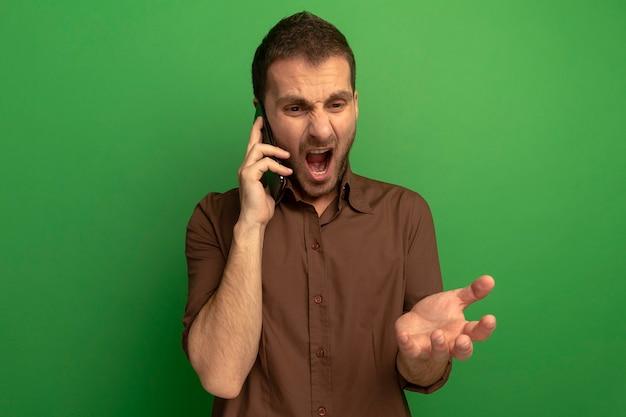 Jovem zangado falando no telefone, olhando para baixo, mostrando a mão vazia isolada na parede verde