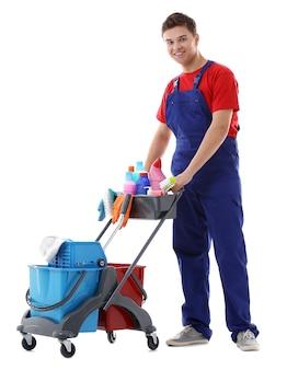 Jovem zelador com carrinho de limpeza, isolado no branco
