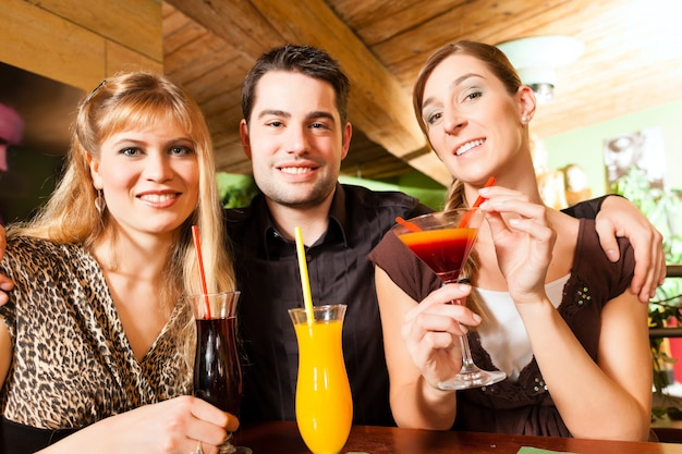Jovens a beber cocktails no bar ou restaurante