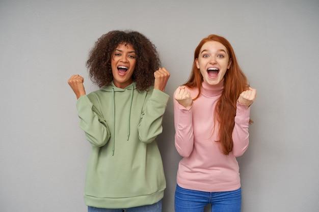 Jovens adoráveis e atraentes mulheres radiantes, erguendo alegremente os punhos enquanto olham emocionalmente com a boca aberta, isolada sobre uma parede cinza