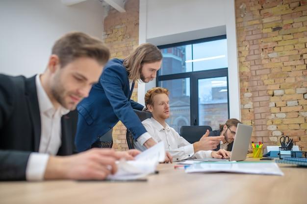 Jovens adultos no escritório trabalhando em um laptop e com papéis