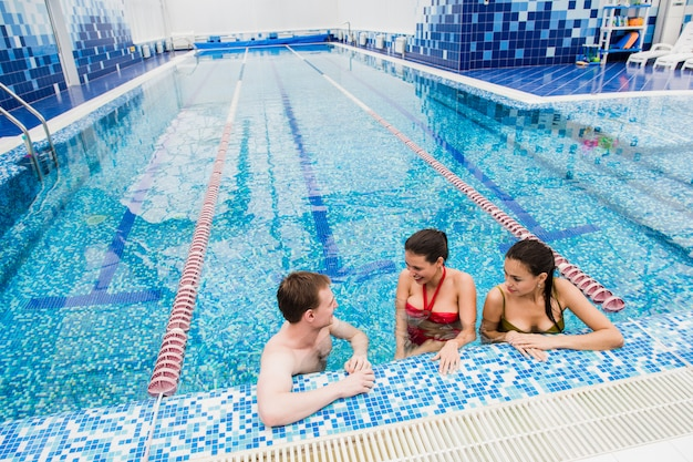 Jovens adultos se divertindo conversando na piscina dentro de casa
