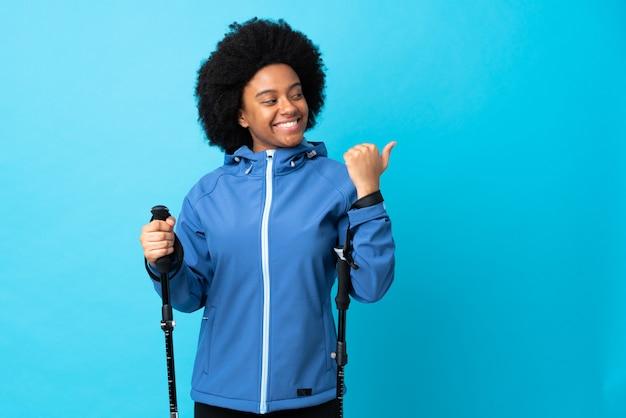 Jovens africanos americanos com mochila e bastões de trekking isolados no azul apontando para o lado para apresentar um produto