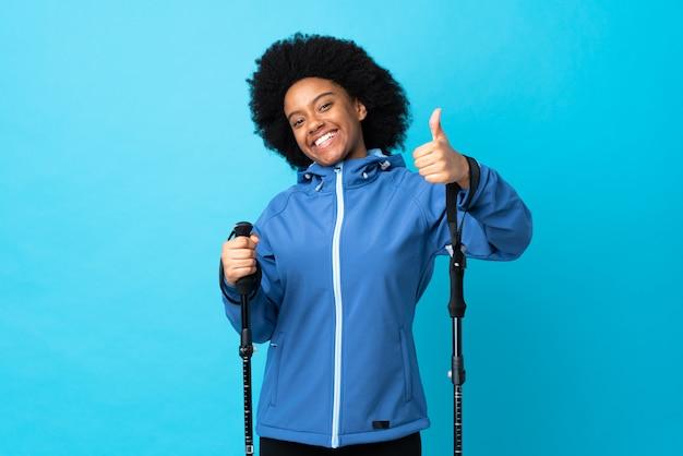 Jovens africanos americanos com mochila e bastões de trekking isolados no azul com polegares para cima, porque algo de bom aconteceu
