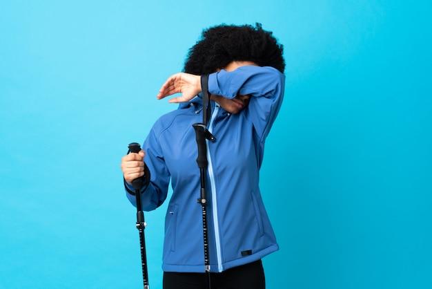Jovens africanos americanos com mochila e bastões de trekking isolados nos olhos de coning azuis pelas mãos