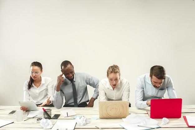 Jovens africanos e caucasianos, homens e mulheres sentados no escritório e trabalhando em laptops. o negócio, emoções, equipe, trabalho em equipe, local de trabalho, liderança, conceito de reunião. emoções diferentes dos colegas