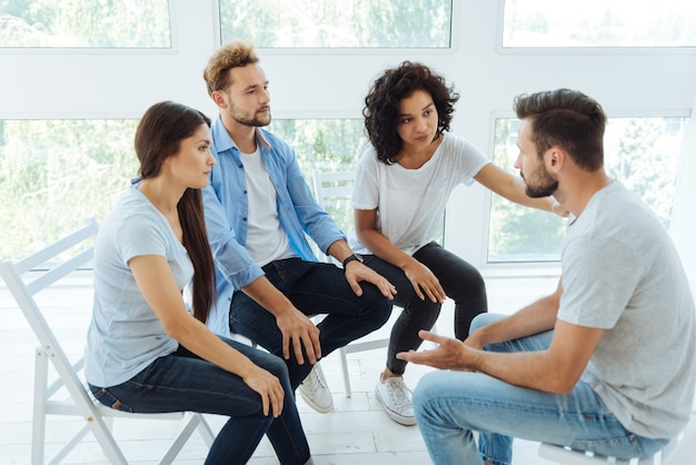 Jovens agradáveis olhando para seu amigo e mostrando seu apoio enquanto ouvem sua história